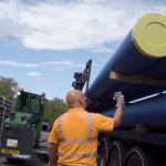 loading blue water pipe onto lorry